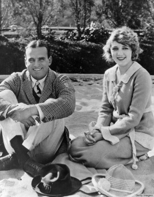 circa 1925:  American actor Douglas Fairbanks, Sr. and his wife, Canadian-born actor Mary Pickford (1893 - 1979) smile while sitting and kneeling in sand.  (Photo by Hulton Archive/Getty Images)